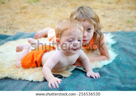 Cut baby boy exploring the world outdoors with his sister - stock photo