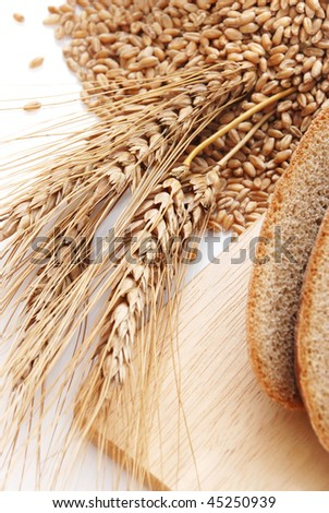 Cut bread and wheat on a wooden surface