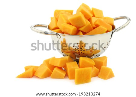 cut  butternut pumpkin blocks in a metal colander on a white background - stock photo