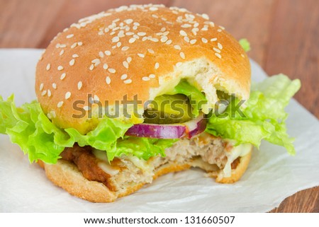 cut cheeseburger on white paper