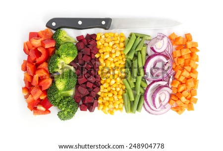 Cut colorful vegetables in line with knife on white background