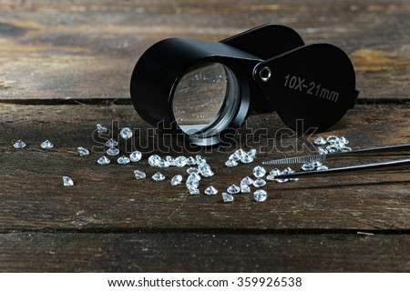 cut diamonds with folding magnifier and tweezers on wooden background - stock photo