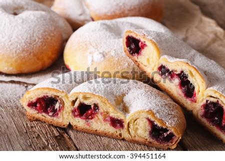 Cut ensaimada bun with berries and powdered sugar close-up on the table. horizontal - stock photo