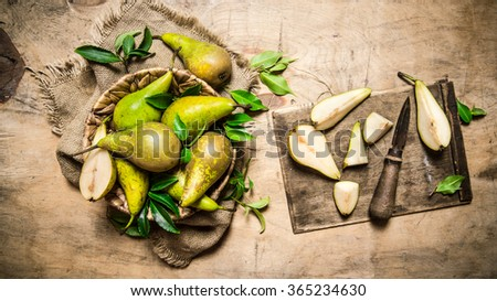 Cut fresh pears on old cutting Board, with a basket full of pears. On a wooden table. Top view - stock photo