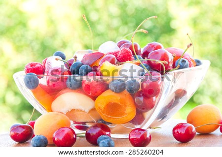 Cut fruits and berries in a glass bowl with ice cubes - stock photo