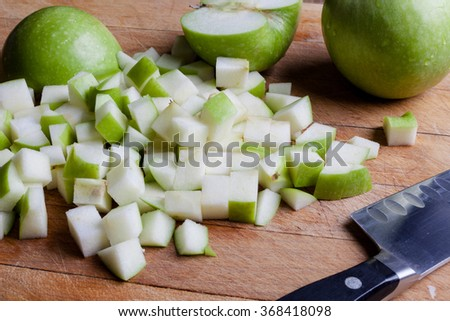 Cut granny smith green apples on wooden cutting board with knife from side - stock photo
