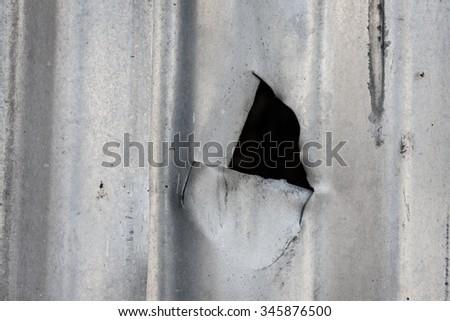 Cut in corrugated metal sheet close-up - stock photo