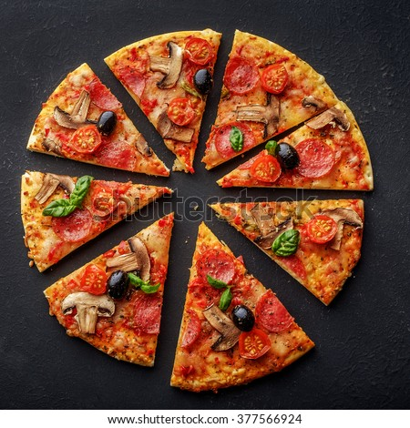 Cut into slices delicious fresh pizza with mushrooms and pepperoni on a dark background. Top view . Pizza on the black table.  - stock photo
