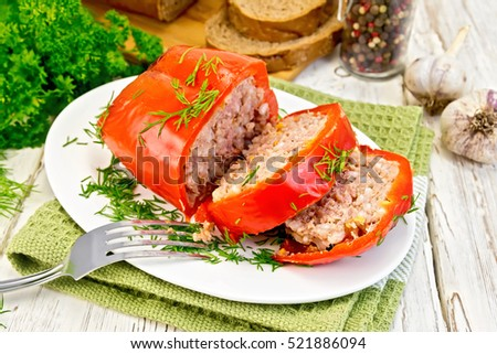 Cut into slices of bell peppers stuffed with meat and rice in a plate on a green napkin, fork, parsley on a wooden boards background
