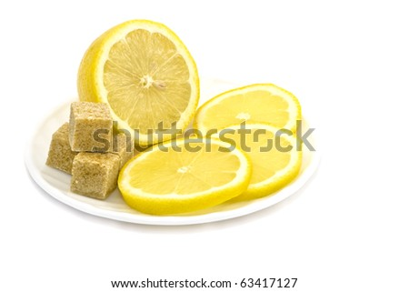 Cut into slices of lemon and slices of brown sugar on a plate on a white background.