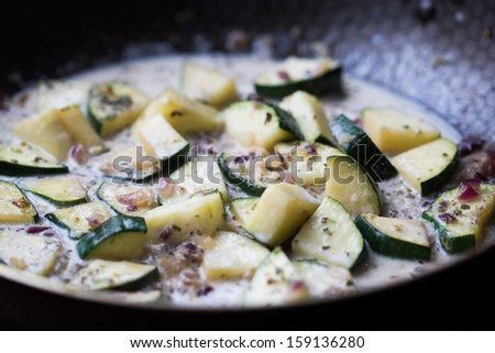 Cut into triangles zucchini fried in creamy sauce with onions and herbs, cooking homemade dinner - stock photo