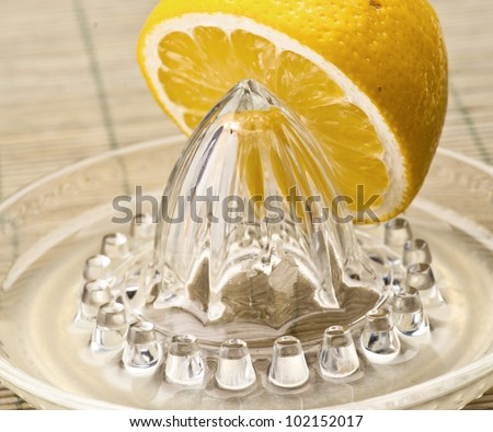 cut lemon on squeezer with wooden background