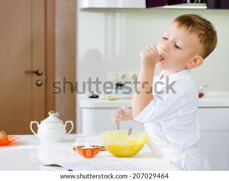 Cut little boy in a chefs uniform tasting his batter mixture sucking on his thumb as he checks the flavour and consistency - stock photo