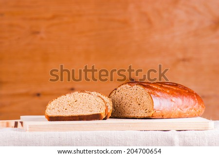 Cut loaf of fresh bread on burlap against wood