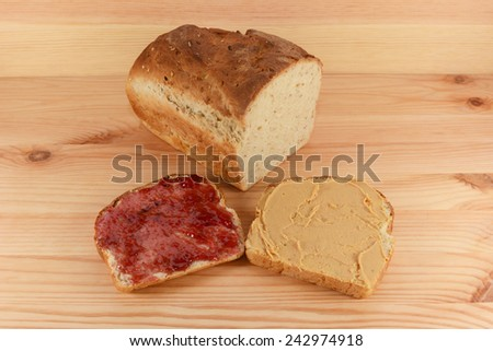 Cut loaf of fresh oat and linseed bread with jam and smooth peanut butter slices on a wooden table - stock photo