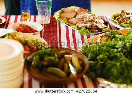 Cut meat and pickled vegetables lay in white dishes on a embroidered cloth in the restaurant - stock photo