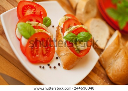 Cut mozzarella cheese and cut fresh tomatos presented on a white plate with tomato and mozzarella sandwich.Surrounded by fresh baguette.