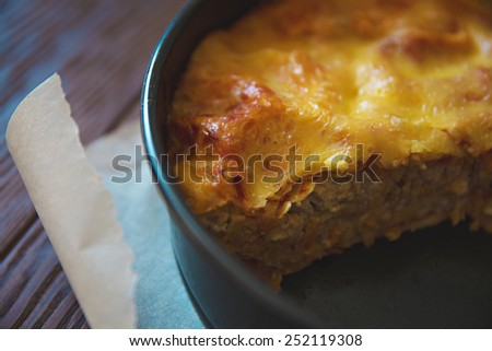 Cut of homemade lasagna on wood - stock photo