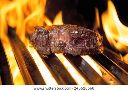 Cut of meat on the barbecue grill, starting to take color, flames all about the steak