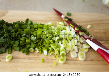 Cut onions for preparation of a lunch on a board with a knife - stock photo