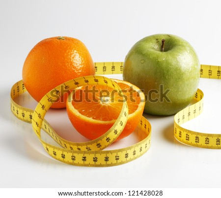 Cut orange and green apple with yellow measure tape - stock photo
