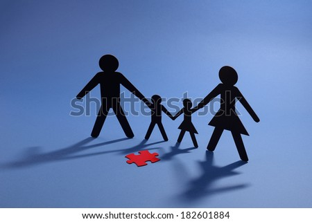 Cut out paper figures of family with red puzzle