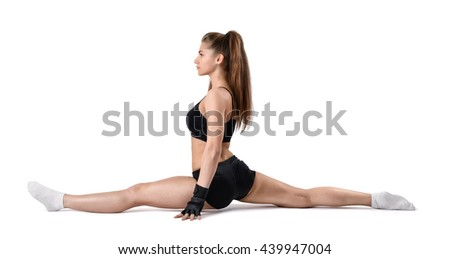 Cut-out portrait of young strong muscular womansitting on the splits. Stretching legs. Studio portrait. Healthy lifestyle. Fitness and sport. Power of body. Sportswear for training.