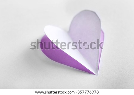 Cut out white paper heart on purple background - stock photo