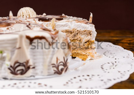 Cut pie with different chocolate ornaments stuffed with condensed milk and nuts on white napkin