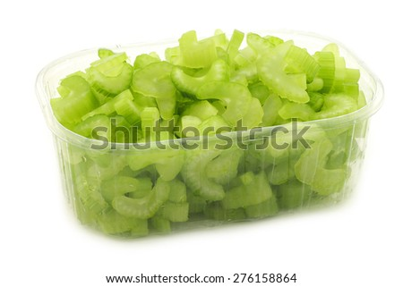 cut pieces of celery in a plastic container on a white background - stock photo