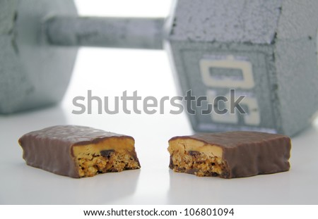 Cut protein bar with 50 pound weight in the background. - stock photo