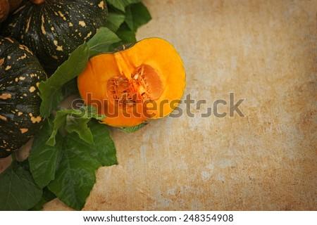 Cut pumpkin beside pumpkins and vines - stock photo