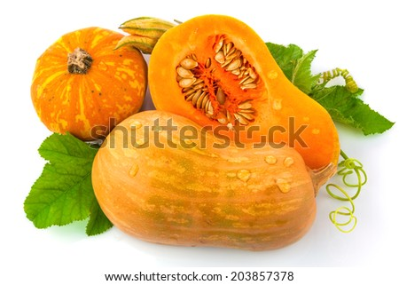 Cut pumpkin with pumpkin seeds and green leaves isolated on white background - stock photo