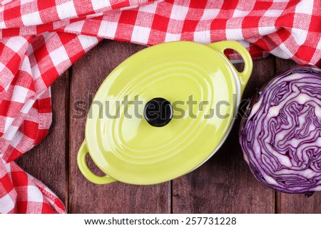 Cut red cabbage and ceramic pot on a table. Kitchen table with utensils. Cook. Top view. Checkered tablecloth, pan and cabbage. - stock photo