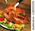 cut roast turkey on wooden table - stock photo