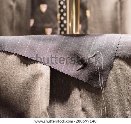 Cut Suit Cloth Pinned with Needle and Thread - stock photo