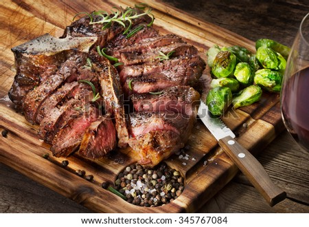 cut t-bone medium-rear steak with brussels sprout on wooden background - stock photo