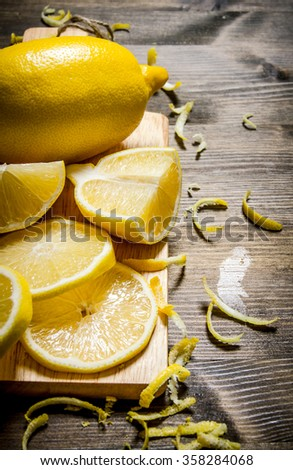 Cut the lemon zest on the Board. On a wooden table. - stock photo