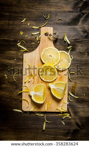 Cut the lemon zest on the Board. On a wooden table. Top view - stock photo