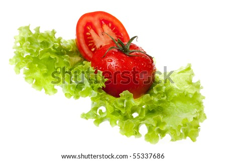 cut tomato on sheet of the salad on white background