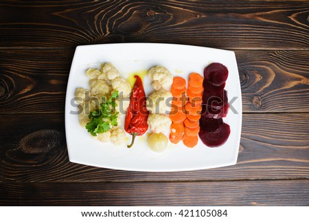 cut vegetables with greens on wooden table - stock photo