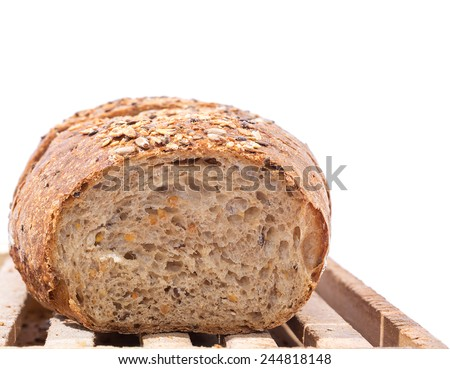 Cut Whole Grain Bread on Wooden Cutting Board over white background - stock photo