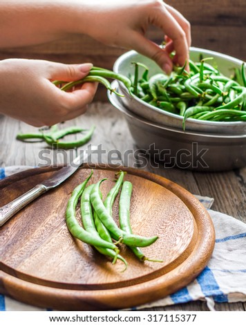 cut with a knife raw green beans on a wooden board, hands, healthy foods