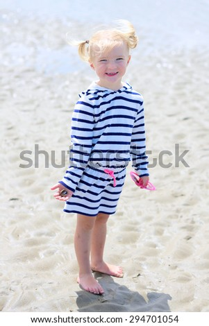 Cute active child playing on sandy beach holding seashells in her hand. Happy little girl enjoying summer holidays on a sunny day. Family with young kids on vacation at the North Sea coast. - stock photo
