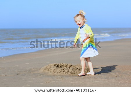 Cute active child wearing colorful dress playing on wide sandy beach. Happy little girl enjoying summer holidays on a sunny day. Family with young kids on vacation at the North Sea coast.