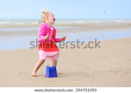 Cute active child wearing pink dress playing and dancing on wide sandy beach. Happy little girl enjoying summer holidays on a sunny day. Family with young kids on vacation at the North Sea coast. - stock photo