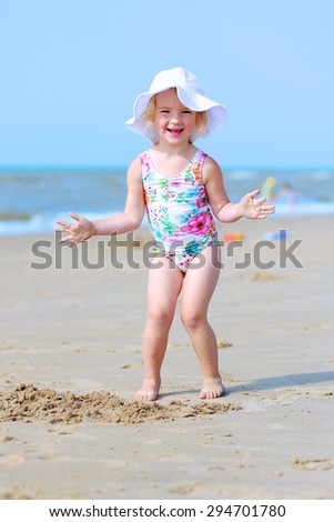Cute active child wearing white hat playing on sandy beach. Happy little girl enjoying summer holidays on a sunny day. Family with young kids on vacation at the North Sea coast. - stock photo