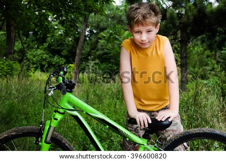 Cute active little boy riding on bike on warm summer day at countryside. Active leisure and sports for kids. Portrait of child, kid with green bicycle looking at camera. Sport, health and fun. - stock photo