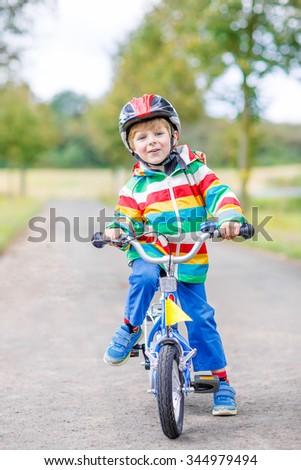 Cute active little boy riding on bike on warm summer day. Countryside. Child in helmet. Active leisure and sports for kids.
