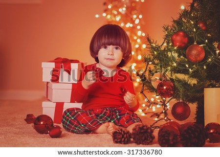 Cute adorable baby boy sitting under decorated illuminated Christmas Tree with gifts. Horizontal with copy space.  - stock photo
